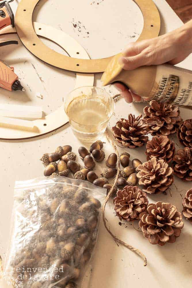 supplies for diy pine cone wreath with acorns laying on work table and lady spraying gold spray paint into a cup of water
