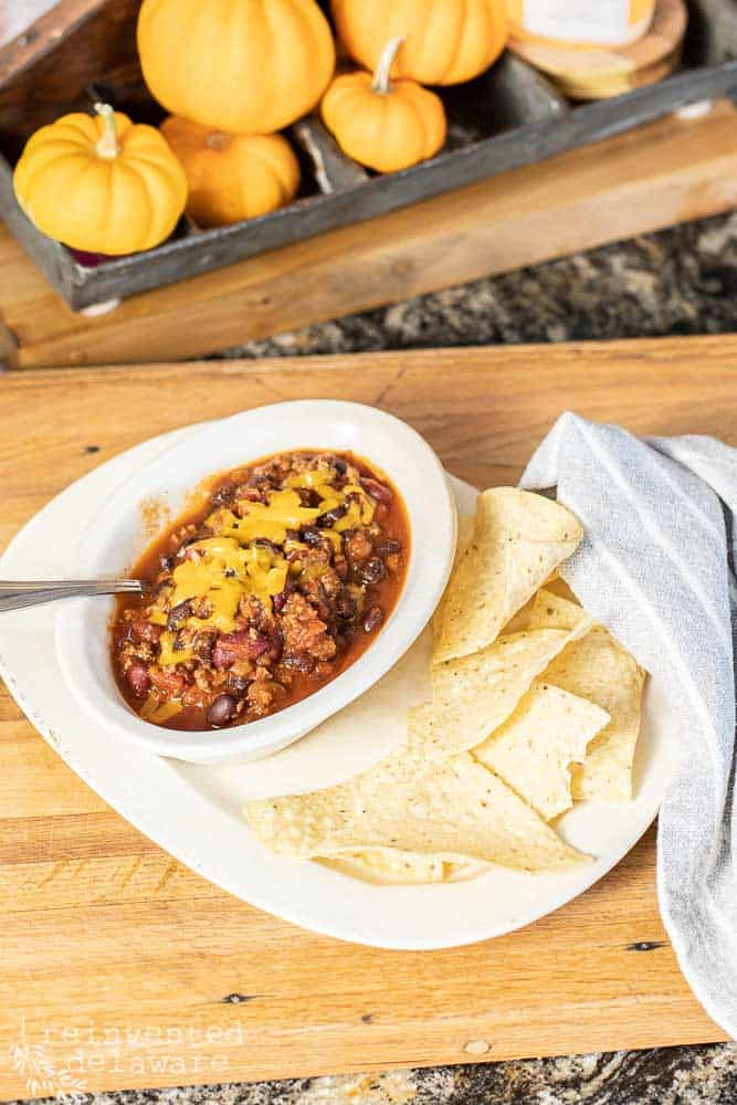 ia bowl of chili on a larger plate with tortilla chips, gray napkin all stiting on a cutting board with small pumpkins in the background