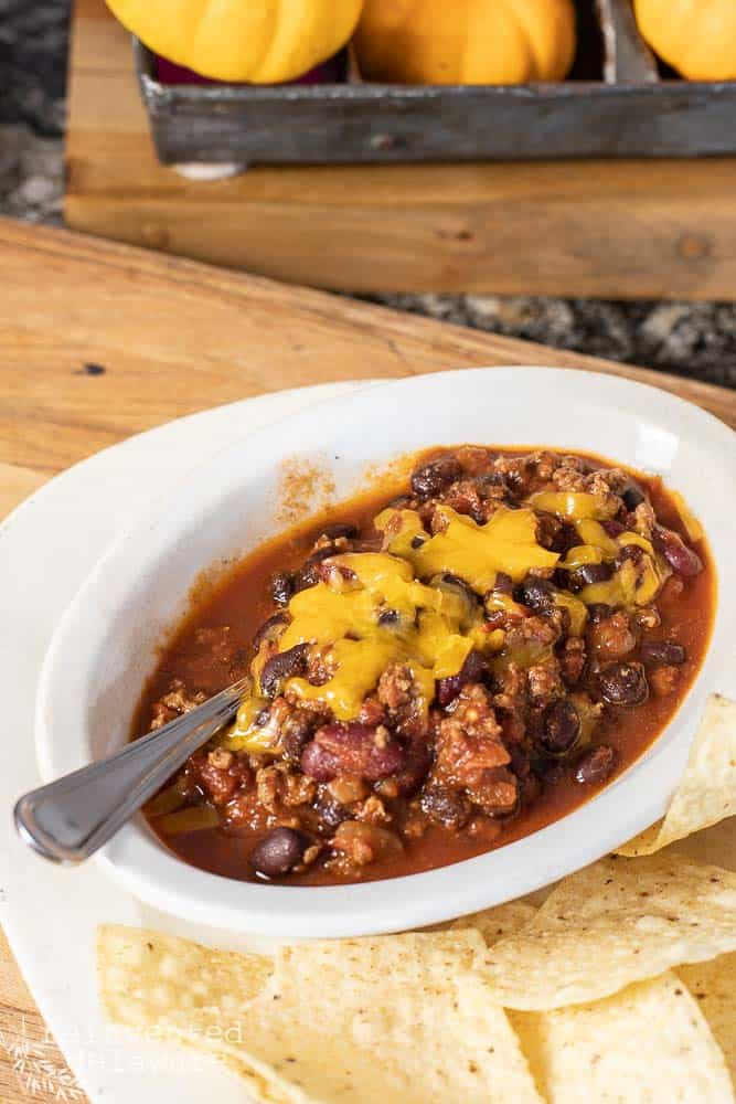 side veiw of a bowl of chili with grated cheddar and chips