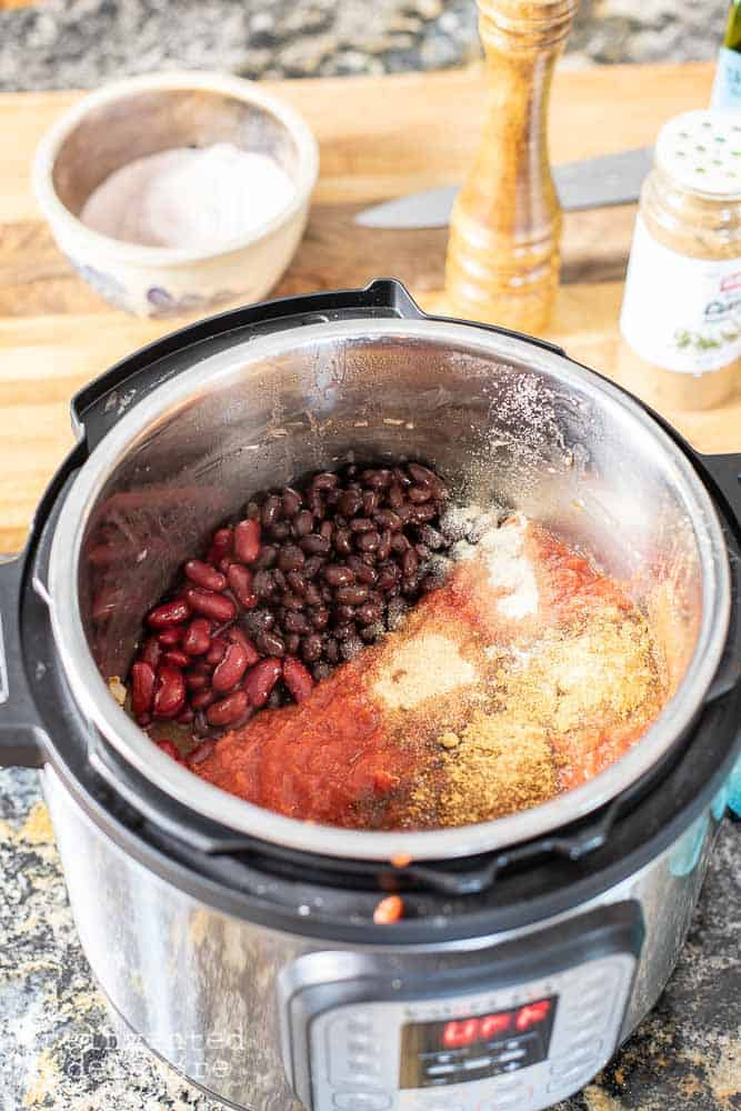 ingredients for an easy bowl of chili in the Instant Pot including beans, meat spices and tomatoes