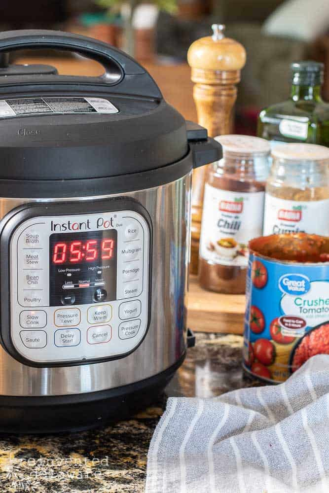 front view on an Instant Pot showing slow cooking feature with spices in the backround and a gray napkin on the side