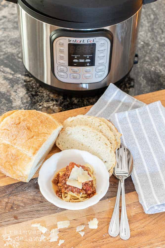 small dish of prepared spaghetti noodles, spaghetti sauce, napkins, silverware and sliced bread with Instant Pot in the background