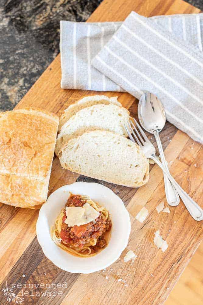 top view of prepared spaghetti dinner with bread, silverware, napkins and a dish of spaghetti