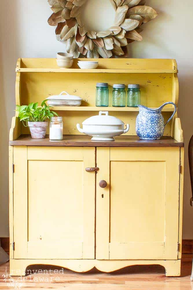 picture of an antique pine cupboard in a tutorial showing how to apply wood paint using milk paint in a yellow color. various items sitting on top of cupboard including a plant, a candle, an ironstone serving dish, a blue pitcher, antique mason jars and several small ironstone and pottery bowls. a magnolia wreath hangs above the painted cabinet
