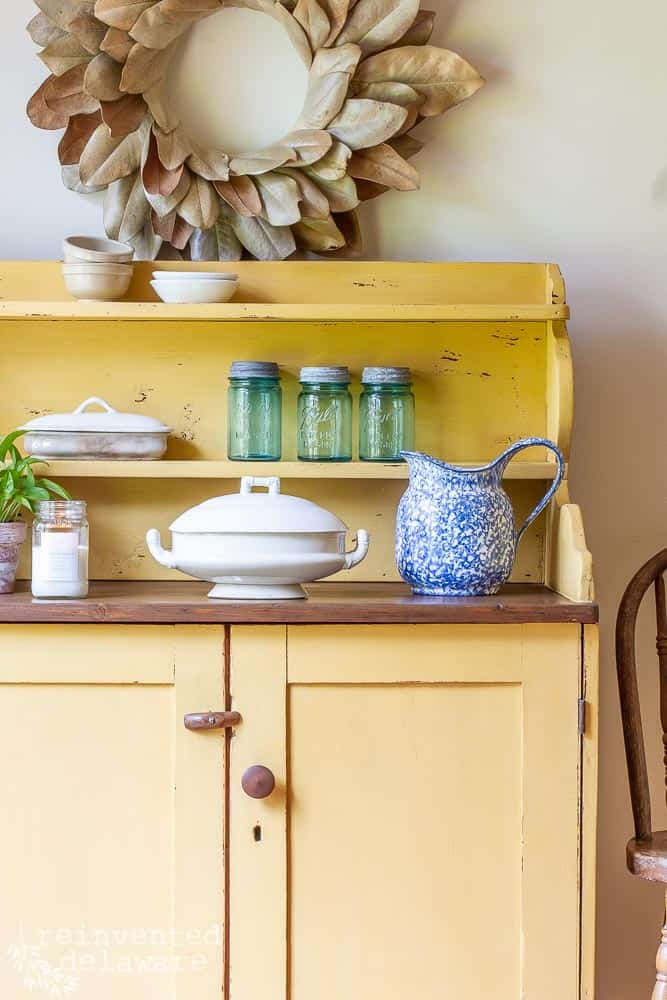 picture of the side of a piece of painted furniture using wood paint in yellow with an ironstone serving bowl, blue pitcher and blue vintage mason jars
