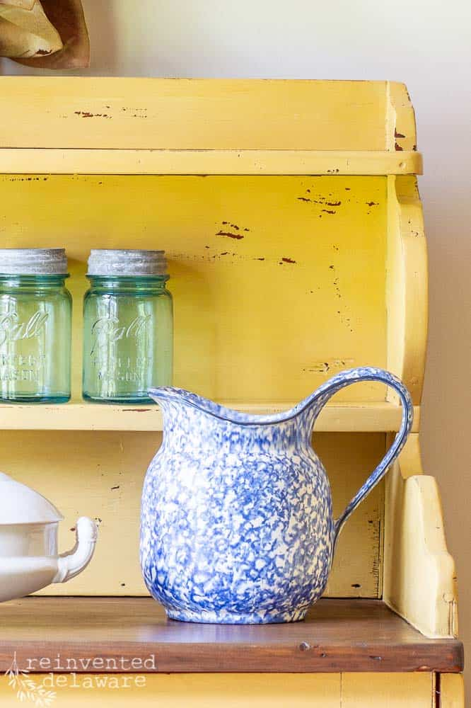 close up picture of vintage cabinet with a blue pitcher sitting on top of the milk painted wood cabinet
