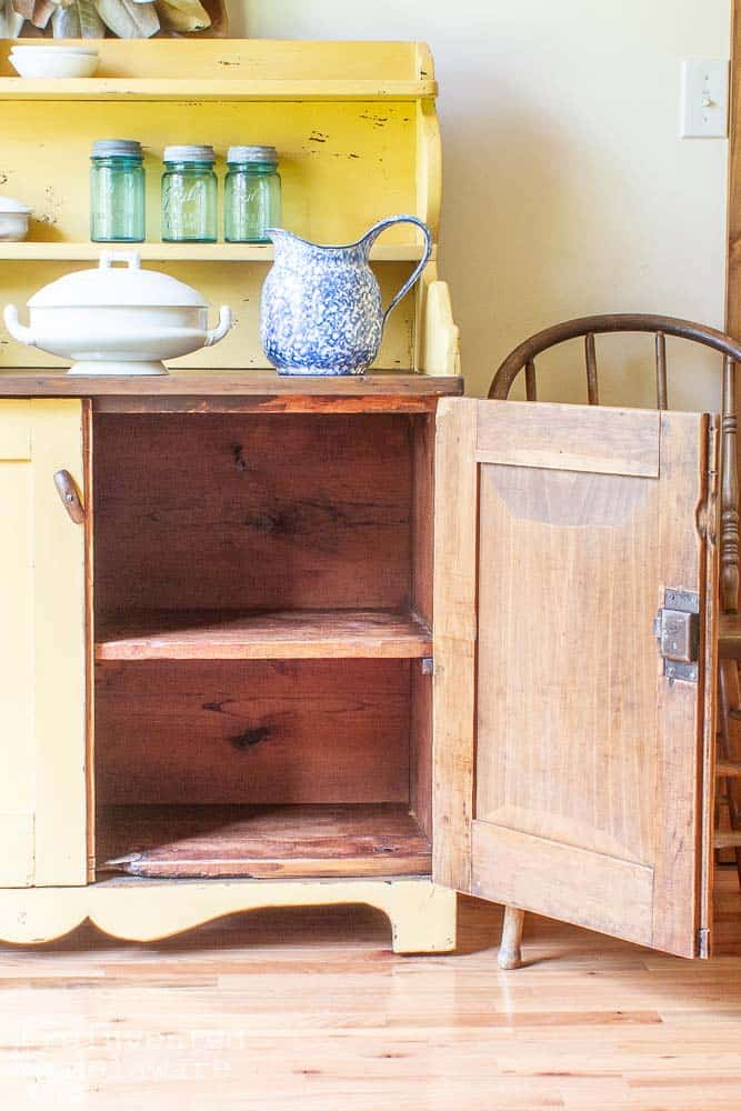 antique cupboard with bottom door open showing storage options. blue pitcher and ironstone serving bowl on top along with three blue mason jars