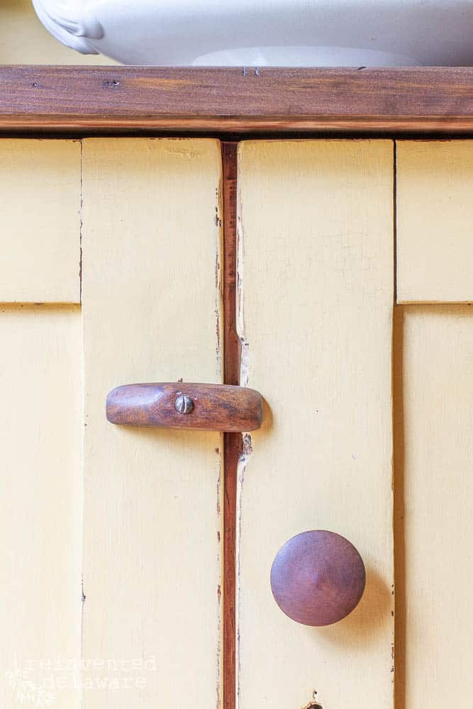 close view of wood hardware on a vintage pine cupboard