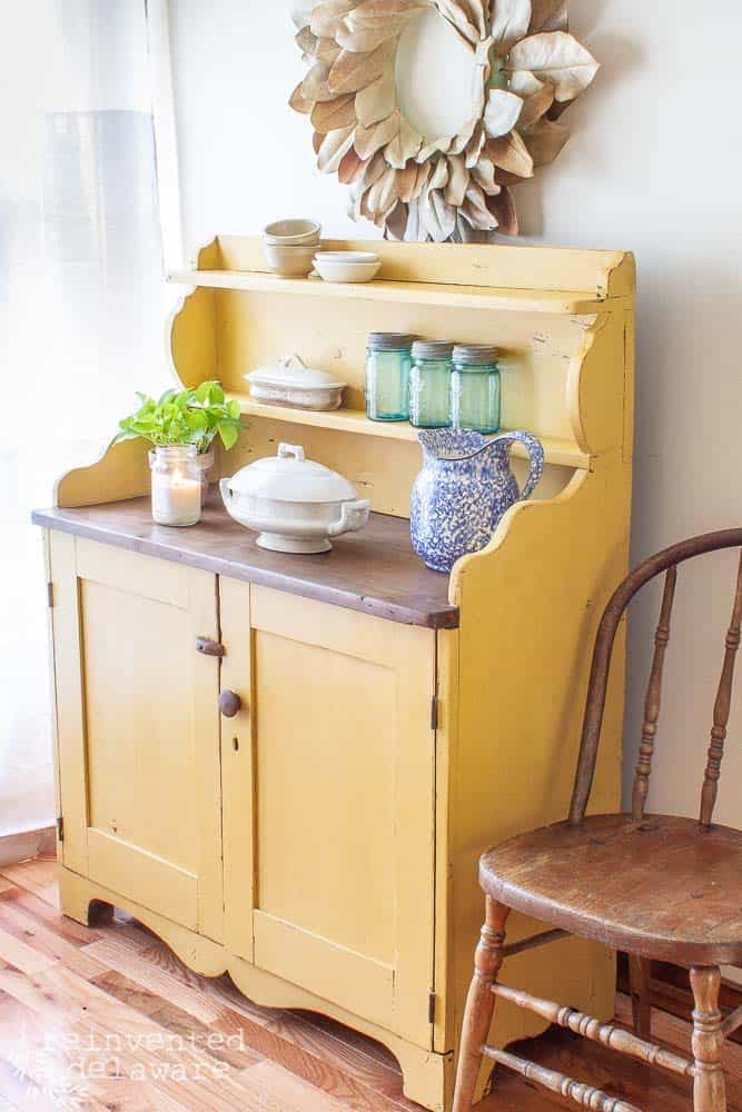side view of a painted wood piece of pine furniture that the wood has been painted in yellow milk paint. The cabinet has various kitchen items staged on to[