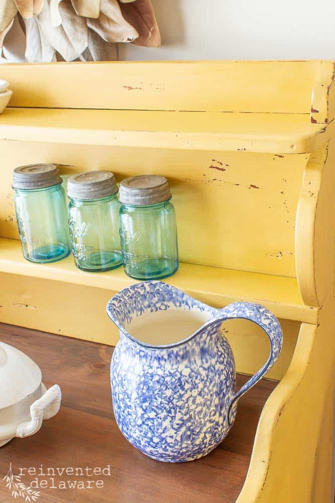 picture of antique pine cupboard painted in milk paint in yellow with a blue pitcher and green mason jars sitting on top