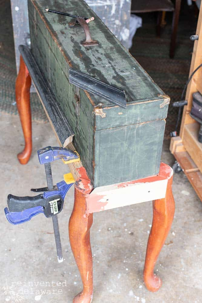 view from top of wood toolbox with lumber, queen anne legs and frame sections glued and held with a furniture clamp