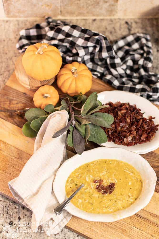 a bowl of chicken corn and butternut squash chowder with bacon bits on the top. a bowl of cooked bacon bits in the background, a sprig of fresh sage, small pumpkins and a buffalo checked towel