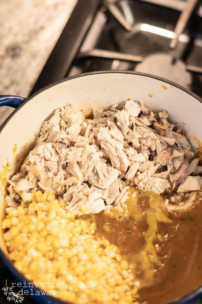 a large dutch oven filled with cooked stock, corn and chopped chicken