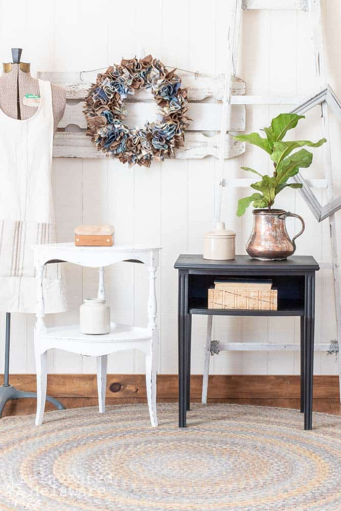 two small tables both with a furniture makeover, one in Dixie Belle Cotton, one in Dixie Belle Midnight Sky for Dixie Belle paint ideas and both are staged with home decor including a wreath on the wall, copper pitcher with a plant, vintage books and a vintage dress form