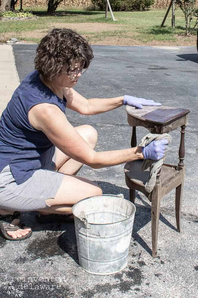 lady scrubbing small table with Dixie Belle White Lightening cleaner outside with a cloth and bucket