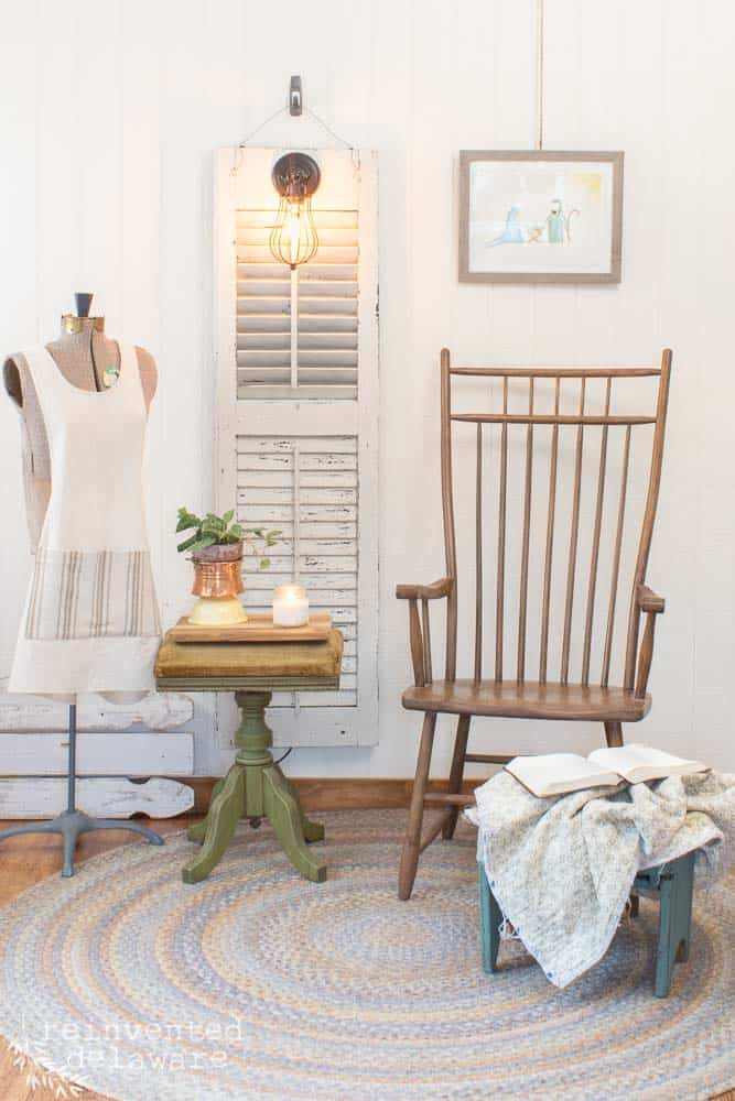 staged scene showing old shutter light that hangs on the wall with a wood chair, a green stool, a footstool with a blanket and a Bible, wall art, and a dress form with a back wrap apron hanging on it