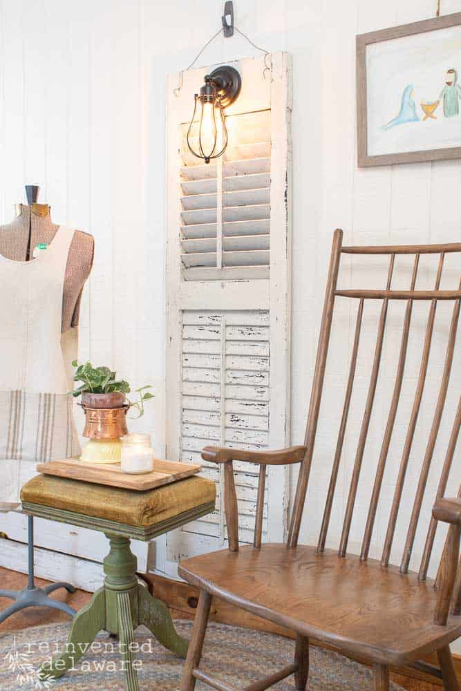 side view of old shutter turned into a hanging wall light fixture with a wood chair, an organ stool and a dress form with an apron hanging on it
