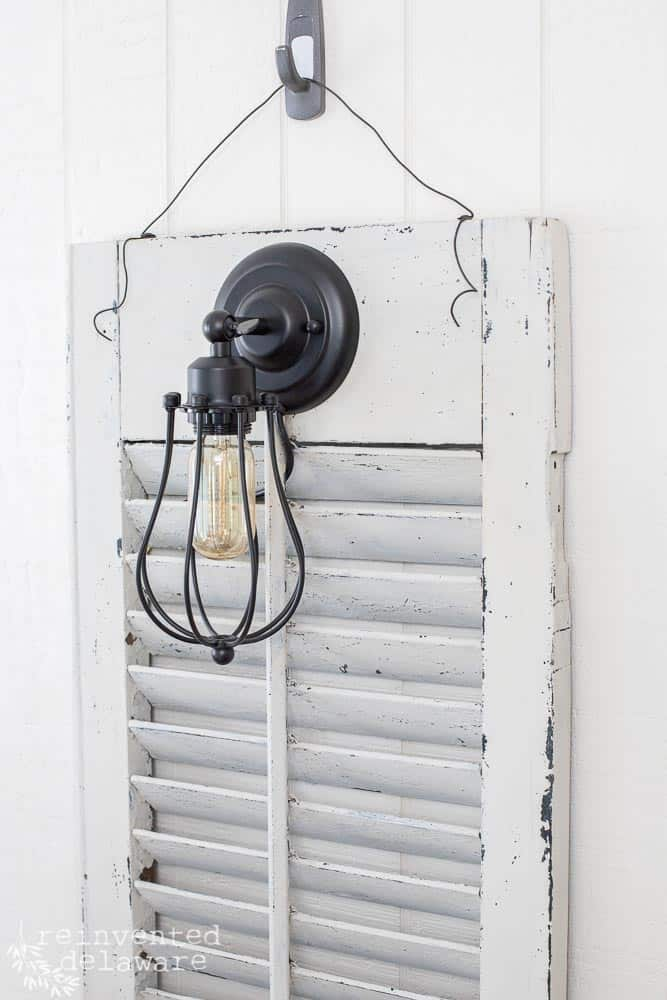 close up of sconce light attached to an window shutter showing ways to use old shutters
