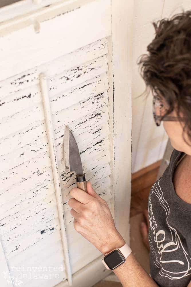 lady chipping paint from an old shutter with a knife