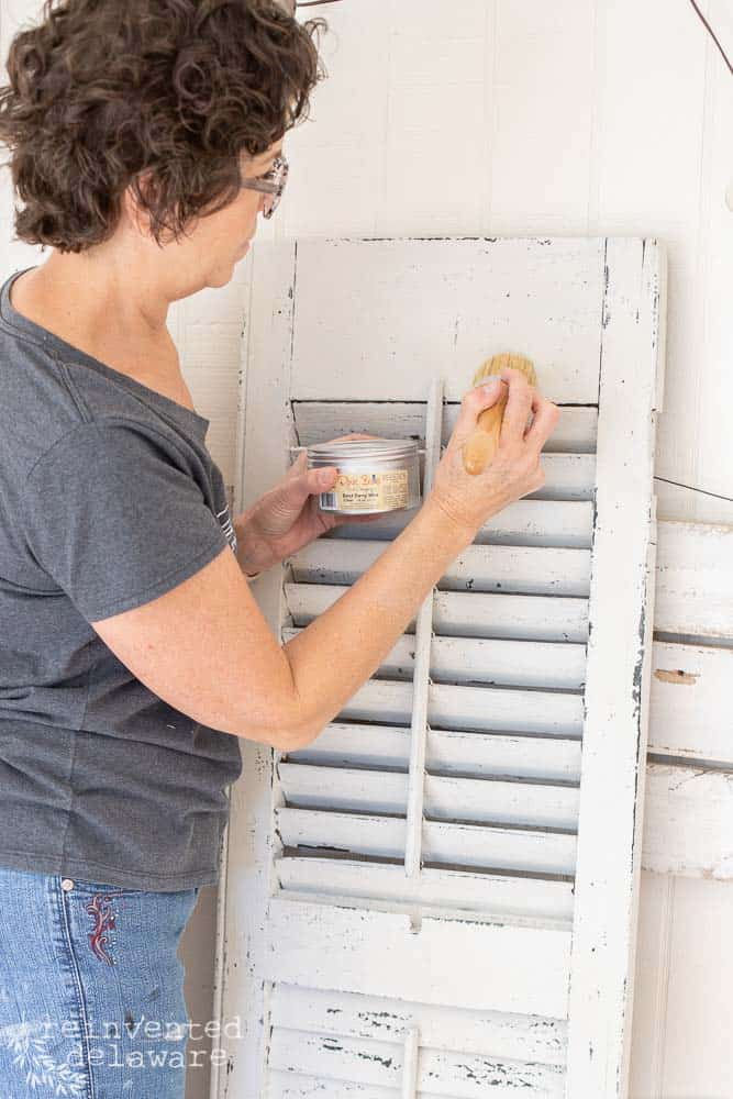 lady waxing an old shutter with Dixie Belle furniture wax