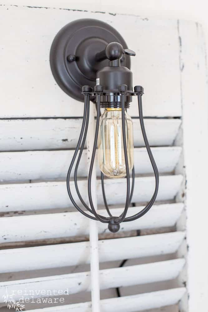 close up view of wall sconce light attached to an old shutter