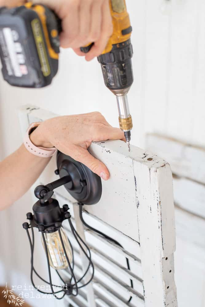lady using a power drill to attach screws on a vintage shutter